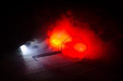 Slut upp det enkla förstoringsglaset med det svarta handtaget som lutar på trätabellen på orange röd rökmörkerbakgrund Overklig b Arkivfoto