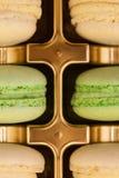 Slut upp färgrika franska makron i en guld- ask arkivbild