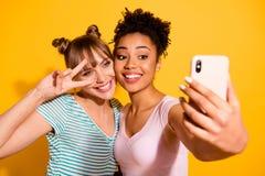 Slut upp för v-tecken för foto för student för två personer för fotoinnehåll överkant för bulle för frisyr för härligt positivt f royaltyfri bild