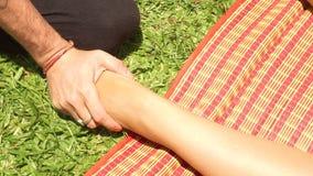 Slut upp fotmassage i utomhus- thai stil Yogamassagiste som gör sträcka fotmassage till kvinnan för att läka och arkivfilmer