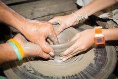 Slut upp fotoet av barnhänder i keramikerhantverk Arkivfoton