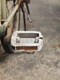 Slut upp fotoet av den gamla, spruckna och rostiga cykelpedalen Arkivfoto