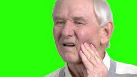 Slut upp gamala mannen som masserar trycka på hans kind stock video