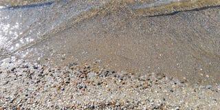 Slut upp Genomskinliga havsv?grullar p? den sandiga stranden arkivfoto