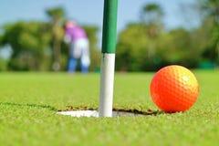 Slut upp golfhålet och en boll på golfbana för grönt gräs Arkivbilder