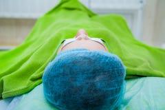 Slut upp härlig kvinnlig patient i säkerhetsexponeringsglas, innan att få en framsidahudbehandling, medan ligga på kosmetologkont Royaltyfri Foto