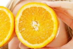 Slut upp hållande apelsiner för kvinna på ögon Royaltyfri Bild