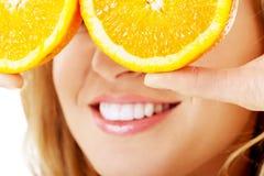 Slut upp hållande apelsiner för kvinna på ögon royaltyfri foto
