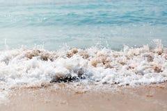 Slut upp havsv?gor med f?rgst?nk p? sandstranden close upp arkivbilder