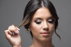 Slut upp horisontalståenden av framsidan för ung kvinna med låset för hår för bullefrisyr som det hållande ser ner allvarligt Arkivbilder
