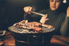 Slut upp kött för kvinnamatlagninggriskött på ett kolgaller i restaura Royaltyfria Bilder