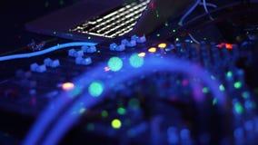 Slut upp konsolen för discjockeykontrollmusik och färgrikt ljus i nattklubb discjockeyblandarespelare och ljudkonsol för diskopar arkivfilmer
