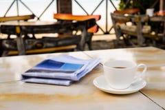 Slut upp koppen för vitt kaffe på den gula tabellen på soluppgångsandstranden med tidningen i morgonen royaltyfri foto