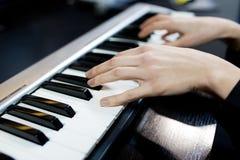 Slut upp kvinnan som spelar pianot royaltyfri foto