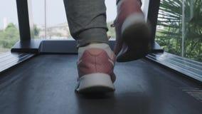 Slut upp kvinnas ben i rosa gymnastikskor på a Treadmill i idrottshallen Glidarekamerar?relse fram?triktat h?rliga ben _ arkivfilmer