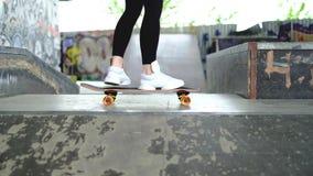 Slut upp längd i fot räknat av en flicka som bär svarta leggins som försöker att rida på en skateboard eller en longboard stock video