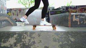 Slut upp längd i fot räknat av en flicka som bär svarta leggins som försöker att rida på en skateboard eller en longboard som fal lager videofilmer
