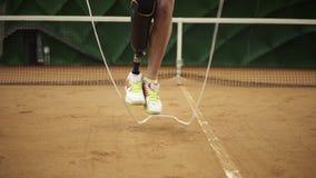 Slut upp längd i fot räknat av en spenslig flicka med ett högert rep för benprotesbanhoppning på en tennisbana i gymnastikskor in lager videofilmer