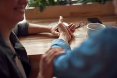 Slut upp lyckliga par som rymmer händer i kafé arkivfoton