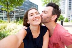 Slut upp lyckliga romantiska par som tar selfie utanför i stad arkivfoto