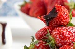 Slut upp, makro Franska Provence Flöden för chokladsås ner på en biten ljus röd jordgubbe fotografering för bildbyråer