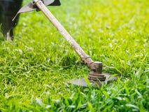Slut upp mannen som mejar gräset arbeta i trädgården för begrepp royaltyfri fotografi