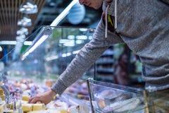 Slut upp mat och ostar för somee för kundhandköpande i marknad fotografering för bildbyråer