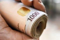 Slut upp nigerianska tusen nairaanmärkningar som är hoprullade i hand royaltyfri bild