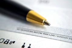 Slut upp på checken med en penna Arkivfoton