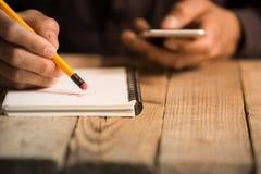 Slut upp på en handstil för hand för man` s på papper med en blyertspenna Royaltyfria Bilder