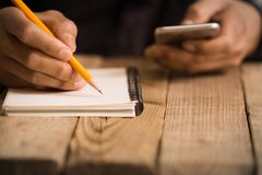 Slut upp på en handstil för hand för man` s på papper med en blyertspenna royaltyfri foto