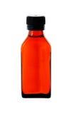 Slut upp på en medicinflaska med röd sirap royaltyfri fotografi