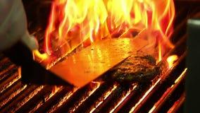 Slut upp på hamburgarematlagning med flamman stock video