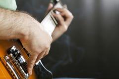Slut upp på handen för man` som s spelar gitarren Arkivbild
