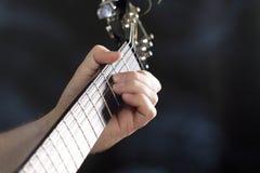 Slut upp på handen för man` som s spelar gitarren Arkivfoto