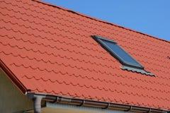 Slut upp på metalltaket med den lofttakfönsterfönstret och avloppsrännan royaltyfri foto