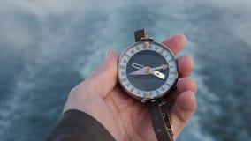 Slut upp p? kompassinstrumentet i behandskad hand Berg som fotvandrar slingor bakgrundsflod lager videofilmer