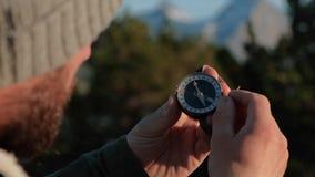 Slut upp p? kompassinstrumentet i behandskad hand Berg som fotvandrar slingor För snubblar begrepp arkivfilmer