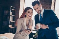 Slut upp partnerkompisar för foto två henne hennes lyssnande affärsdam honom honom hans grabb att berätta att tala skoja humorist royaltyfri fotografi