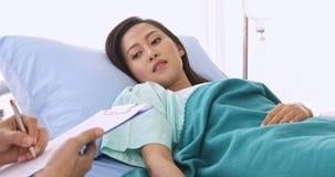 Slut upp platsvideoen av doktorn som fr?gar asiatisk kvinnlig patient om hennes sjukdom i sjukhus arkivfilmer