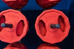 Slut upp röda viktplattor i idrottshallslut arkivfoto