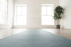 Slut upp rullad ut yoga som är matt på golv i tomt rum arkivfoton
