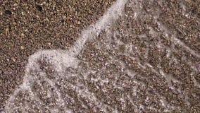 Slut upp sandstranden för bästa sikt, genom att vinka havsvatten långsam rörelse arkivfilmer
