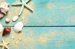 Slut upp Sjöstjärna, snäckskal och sand på en träblå bakgrund royaltyfri fotografi