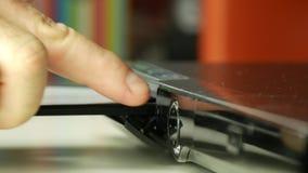 Slut upp skytte med manhanden som sätter in en CD i spelare stock video