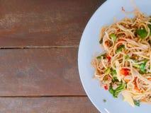Slut upp spagetti på den vita plattan olivgrön för olja för kök för kockbegreppsmat ny över hällande restaurangsallad Royaltyfri Fotografi