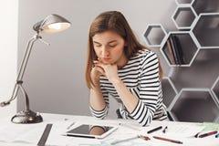 Slut upp ståenden av den härliga unga allvarliga kvinnliga arkitektstudenten med brunt hår i den randiga blicken, hållande huvud  Royaltyfri Fotografi