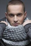 Slut upp ståenden av den unga stiliga mannen i ett ljus - grå färgsjal som är sh Royaltyfria Bilder