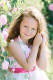 Slut upp ståenden av en gullig lockig litet barnflicka som är utomhus- i en rosträdgård som luktar blommorna Arkivfoton