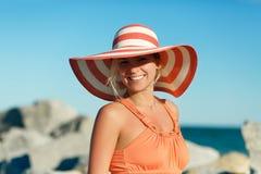 Slut upp ståenden av kvinnan i orange klänning på havsstranden arkivfoton